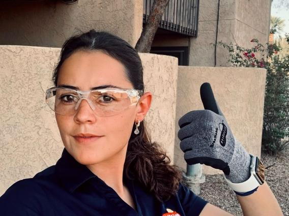 woman wit brown hair in safety goggles giving a thumbs-up