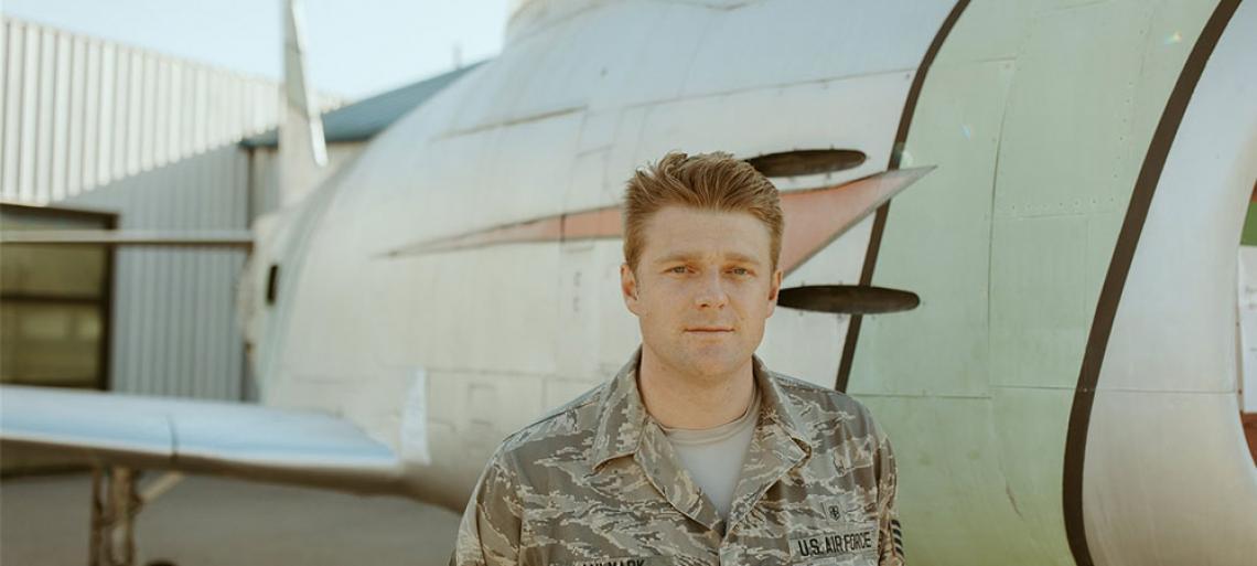 Military man standing next to plane