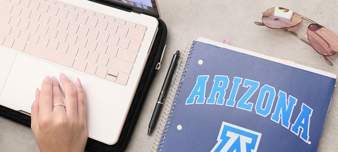 Hand on laptop computer with University of Arizona notebook