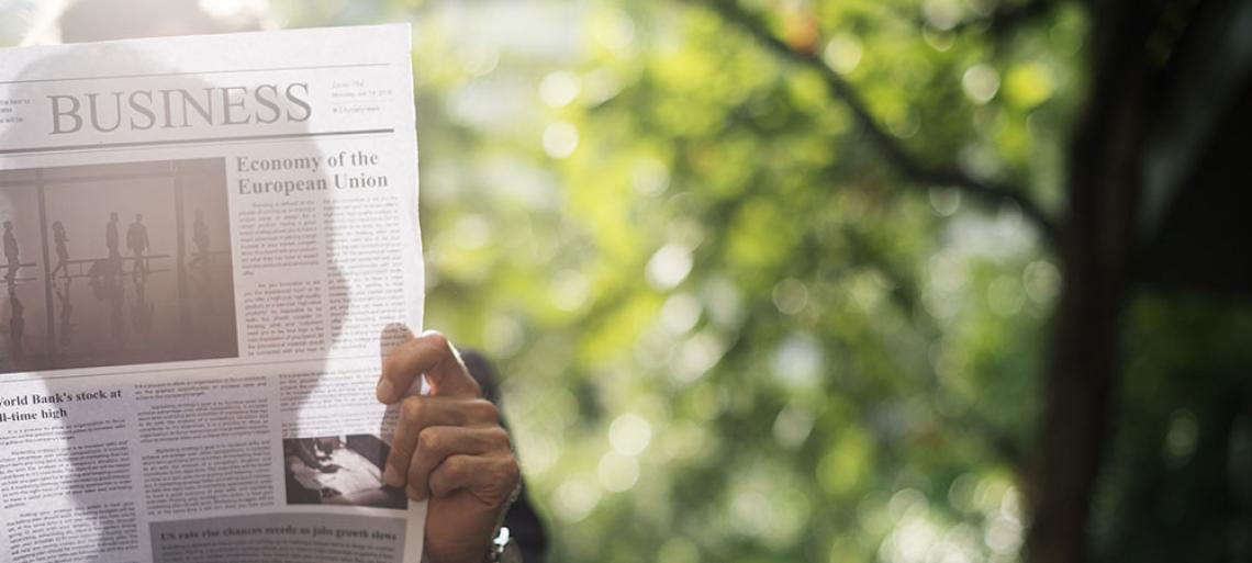 Person reading business section of newspaper